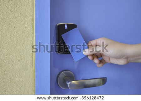 hand hold key card touch on black electronic key pad lock access control with stainless steel door handle on blue door - stock photo