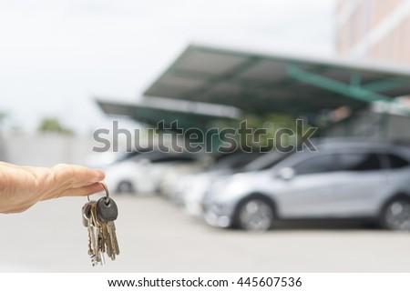 Hand hold keys on blur car parking - stock photo