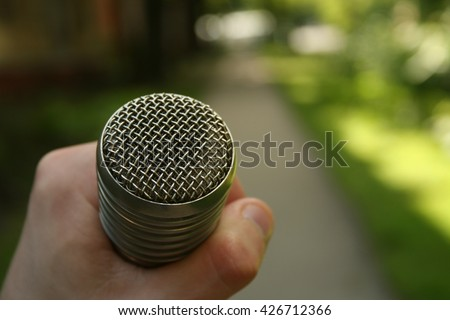 Hand hold microphone. Interview in the summer park.