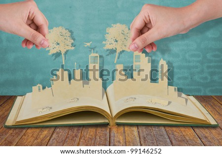Hand hold paper cut  of tree over Paper cut of cities with car and plane on old book - stock photo
