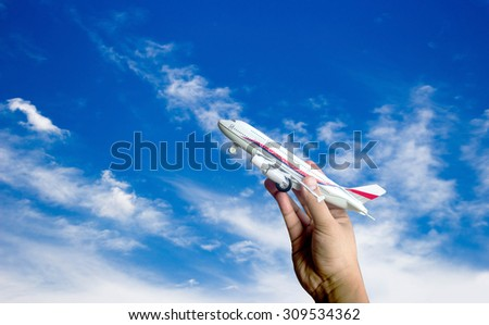 hand hold plane toy on blurred clear sky for background