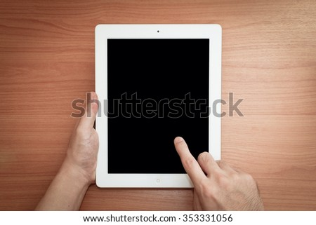 hand hold portable tablet and finger touching on screen, work desk