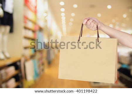 hand hold shopping bag in clothing store - stock photo