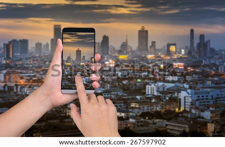 hand hold smart phone capture the images on the sunset city background - stock photo