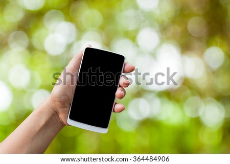 hand hold smart phone,cell phone,mobile over blurred image of green background - stock photo