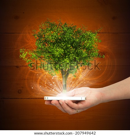Hand hold smart phone with magical green tree - stock photo