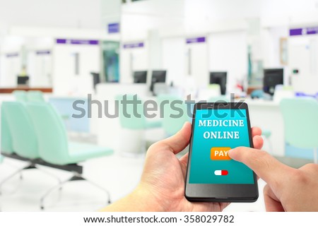 hand hold smartphone and finger touch pay button on screen for medicine online payment via application with blur cashier counter at hospital - stock photo