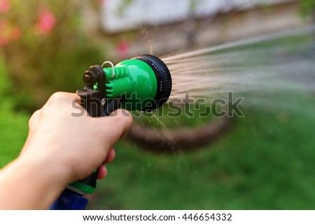 hand hold sprinkler water hose to irrigate garden