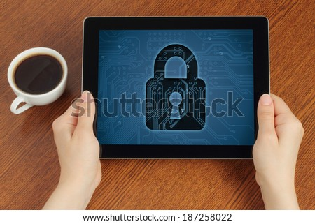 Hand hold tablet pc with lock on wooden background   - stock photo