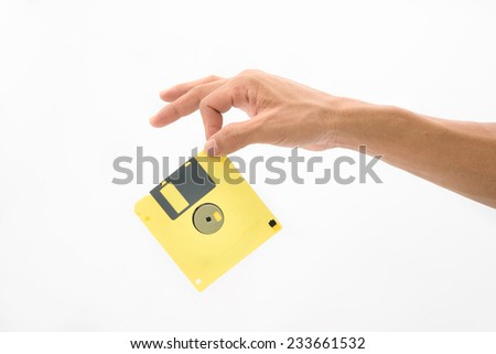 Hand hold yellow floppy disc on isolated white background - stock photo