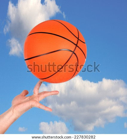 Hand holding a basketball with a beautiful sky behind - stock photo