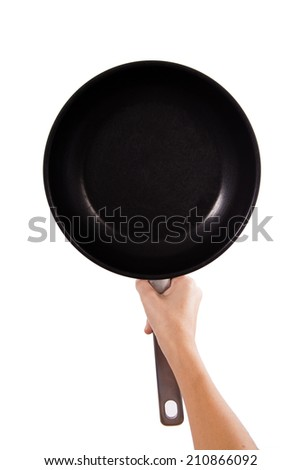 Hand holding a black Old frying pan - stock photo