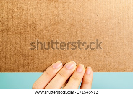 Hand holding a blank cardboard message on blue background - stock photo