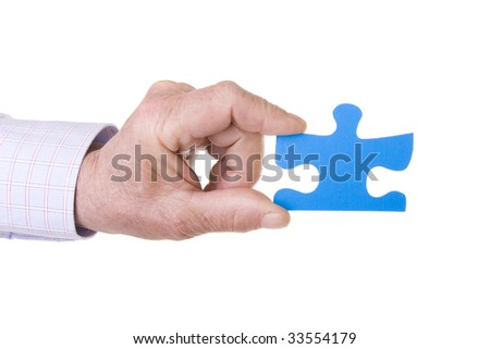 Hand holding a blue puzzle isolated on white