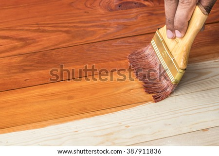hand holding a brush applying varnish paint on a wooden surface - stock photo