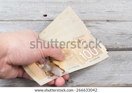 Hand holding a bunch of brown bank notes on a wooden table - stock photo
