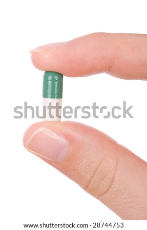 Hand holding a capsule or pill close up