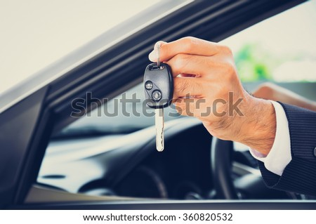 Hand holding a car key - car sale & rental business concept, vintage tone - stock photo