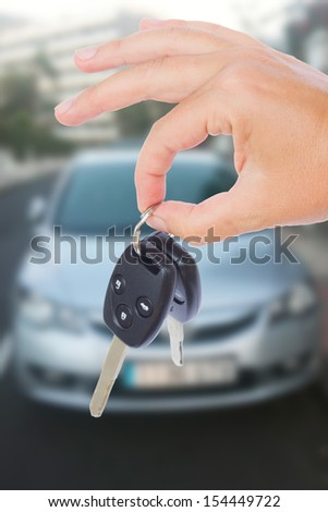 hand holding a car keys with a car on background