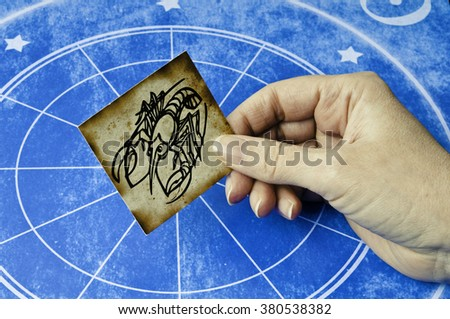 hand holding a card with sign of cancer - stock photo