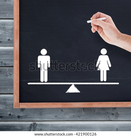Hand holding a chalk and writing something against blackboard with copy space on wooden board - stock photo