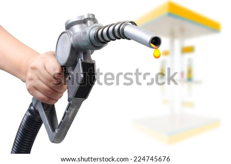hand holding a classic fuel nozzle pumping a benzine fuel at gas station - stock photo