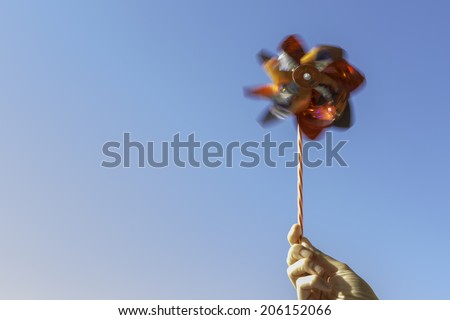 hand holding a colored pinwheel rotating on a blue sky background - stock photo
