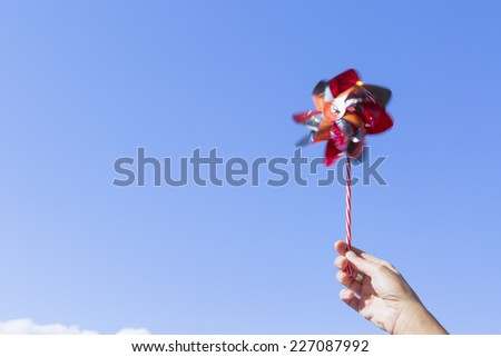 hand holding a colored pinwheel rotating on a blue sky background on a sunny day - stock photo