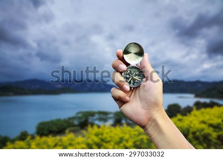 Hand holding a compass on natural background - stock photo