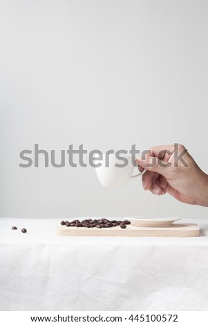 Hand holding a cup of coffee with coffee beans on wooden tray on white table