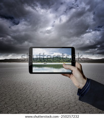 Hand holding a digital tablet in a desert with a lake on the screen  - stock photo