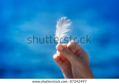 Hand holding a feather in front of blue natural background - stock photo