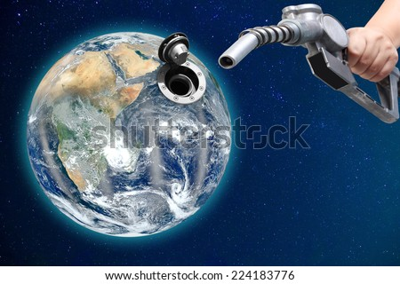 hand holding a gasoline classic fuel nozzle with globe conceptual image energy  Elements of this image furnished by NASA - stock photo