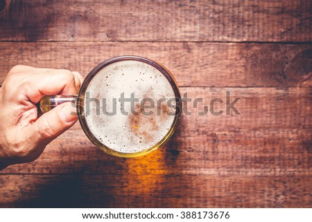 Hand holding a glass of beer on wooden table - stock photo