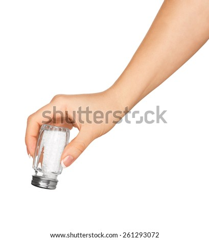 hand holding a glass saltcellar with salt isolated on a white background - stock photo