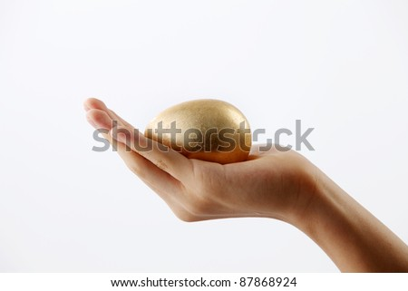 Hand holding a golden egg