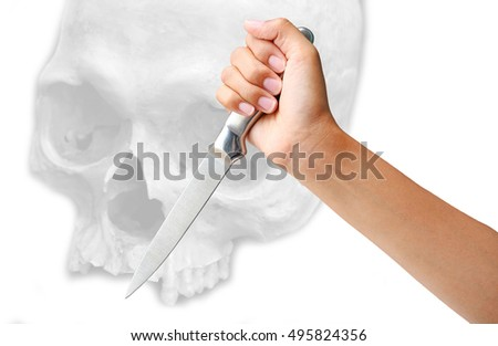 hand holding a knife ready to strike down against skull on white background