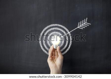 Hand holding a lightbulb on dartboard sketched blackboard - stock photo
