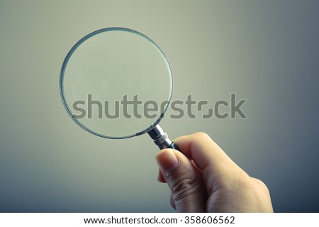 Hand holding a magnifying glass with blank background. - stock photo