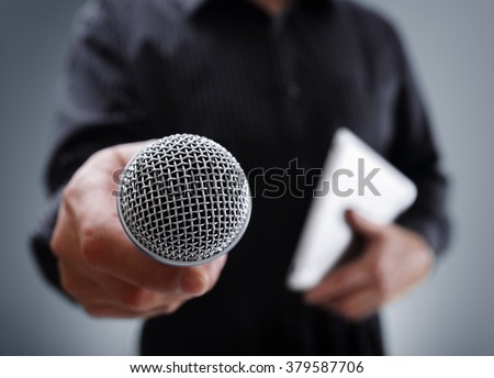 Hand holding a microphone conducting a business interview or press conference - stock photo