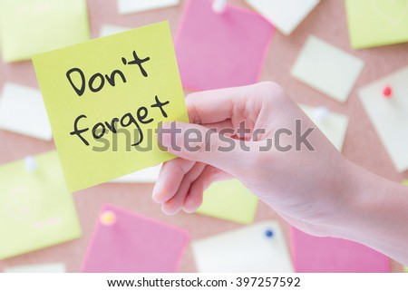 hand holding a notepaper or post it with words don't forget - stock photo