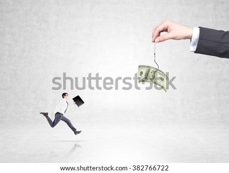 hand holding a one-hundred dollar banknote on a thread, a young businessman with a case running to it. Concrete background. Concept of motivation. - stock photo