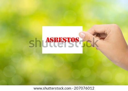 Hand holding a paper ASBESTOS on green background - stock photo