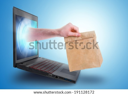 Hand holding a paper bag coming out of a laptop screen - Internet shopping concept. - stock photo