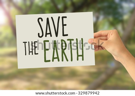 Hand holding a paper card with Save the Earth word on abstract nature background
