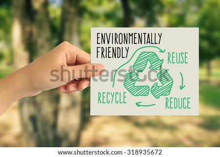 Hand holding a paper card with the recycling sign on abstract nature background - stock photo