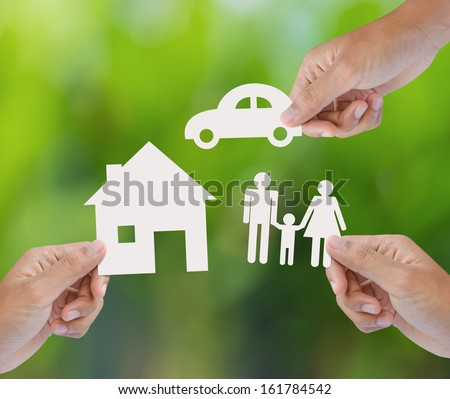 Hand holding a paper home, car, family on green background, insurance concept - stock photo