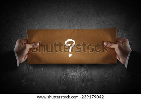 Hand holding a paper with question mark - stock photo