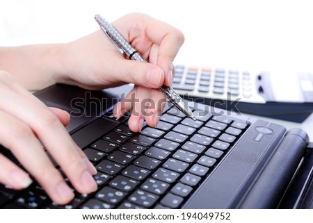 Hand holding a pen and typing keyboard - stock photo