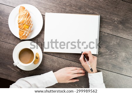 hand holding a pen. Top view. Table with notepads, cup of coffe and croissant . empty white space you can put your text.  - stock photo
